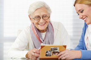 25216456 - happy senior woman watching photo album with eldercare nurse