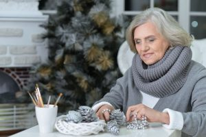 65629470 - portrait of senior woman sitting at the table with christmas decorations