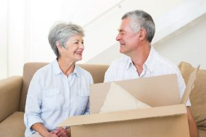 27195496 - cheerful senior couple moving into new home smiling at each other
