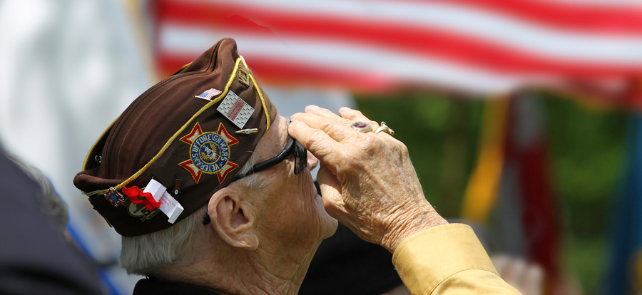 Image of elderly veteran in foreground facing the right and saluting with an American Flag in the background.